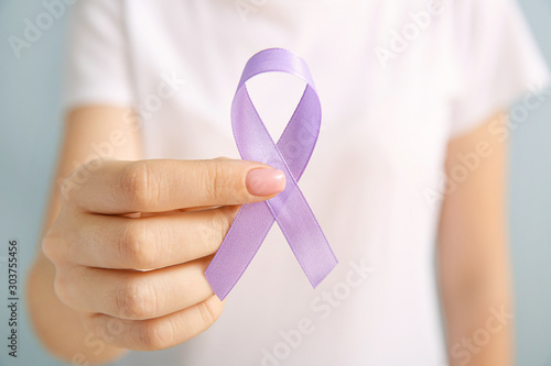 Young woman with lilac ribbon on grey background, closeup. Cancer awareness concept