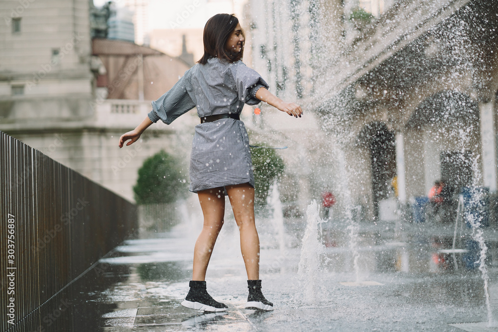 Fototapety, obrazy: girl playing and dancing around on a wet street of Chicago