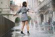 girl playing and dancing around on a wet street of Chicago