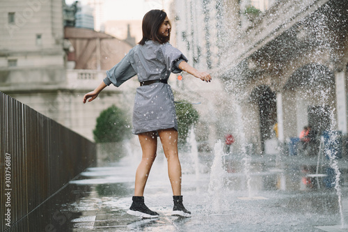 Obraz girl playing and dancing around on a wet street of Chicago - fototapety do salonu