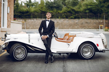 Elegant Fiance In A Black Suit. Man Standing Near Old Car