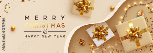 Fototapeta Christmas banner. Background Xmas design of sparkling lights garland, with realistic gifts box, glitter gold confetti. Horizontal New Year poster, greeting card, header, website. Design Flat top view obraz