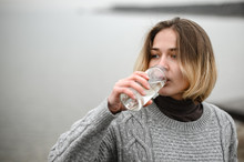 Young Girl In A Warm Woolen Sweater Drinks Clean Water From A Reusable Glass Bottle By The Sea
