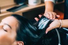 Hairdresser's Hands Applying Conditioner