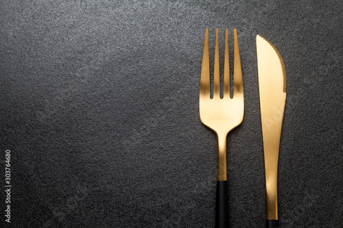 Fotografering Fork and knife on a empty  black plate. Close-up.