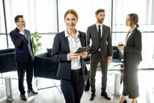 Portrait Of A Beautiful White Collar Busines Woman Standing In Front Of Business Team At The Luxurious Office