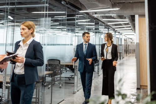 Fototapety, obrazy: Group of business people strictly dressed in the suits meeting in the hallway of the modern office building, white-collar workers having informal discussion indoors