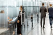 canvas print picture - Business people walking in the hallway of the modern office building with employees working behind glass partitions. Work in a large business corporation