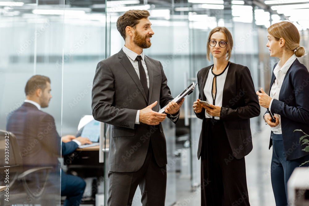 Fototapeta Business people talking in the hallway of the modern office building with employees working behind glass partitions. Work in a large business corporation