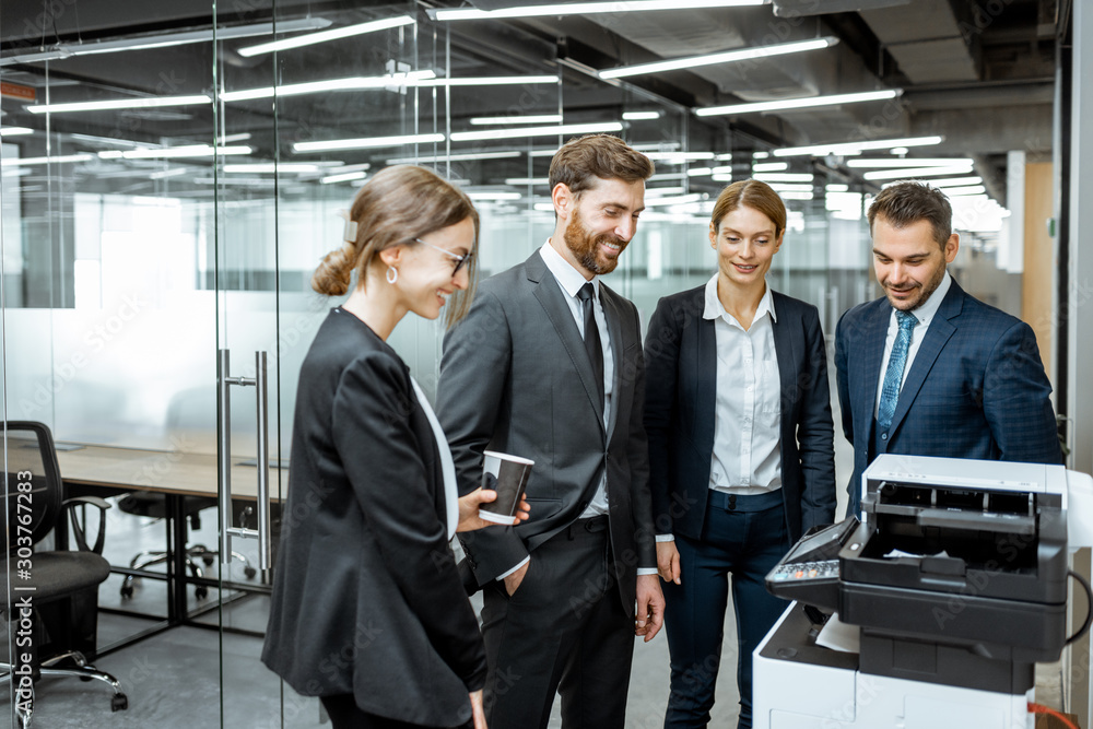 Fototapeta Group of business people hanging out together near the copier during a coffee break in the hallway of the big corporation