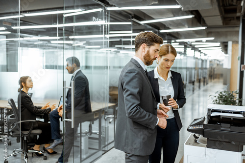 Fotografiet Business man and woman talking near the copier during a coffee break in the hall