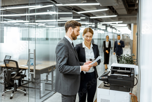 Canvastavla Business man and woman talking near the copier during a coffee break in the hall