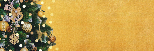 Fototapeta Golden holidays banner with decorated Christmas tree branches and bright bokeh. New Year background with copy space.  obraz