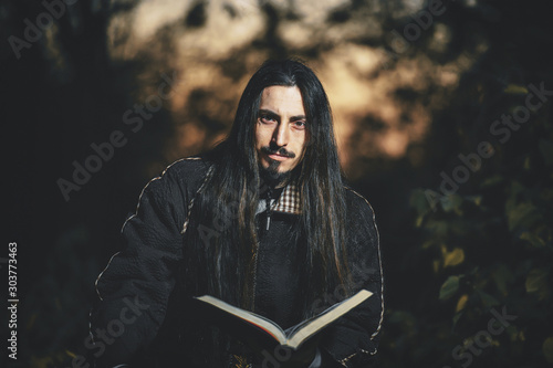 Photo A man with long hair and beard in a black cloak in the image of a sorcerer warlock on Halloween