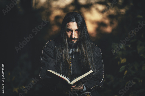 A man with long hair and beard in a black cloak in the image of a sorcerer warlock on Halloween Canvas Print