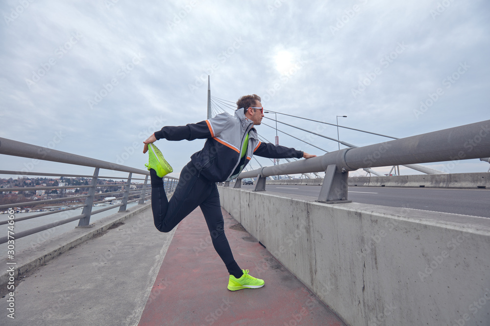Fototapety, obrazy: Sportsman working out / jogging on a big city urban bridge.