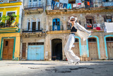 Stylish woman in a white suit and white hat dancing on an city street of Cuba