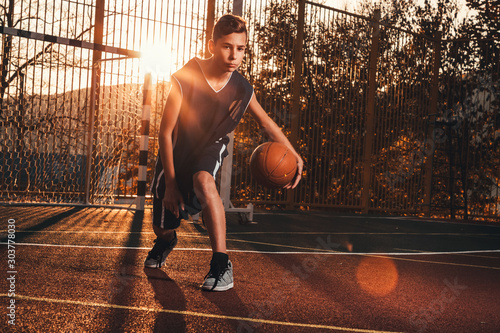 Sports and basketball. A young teenager in a black tracksuit is playing a basketball. Sunset light. Copy space