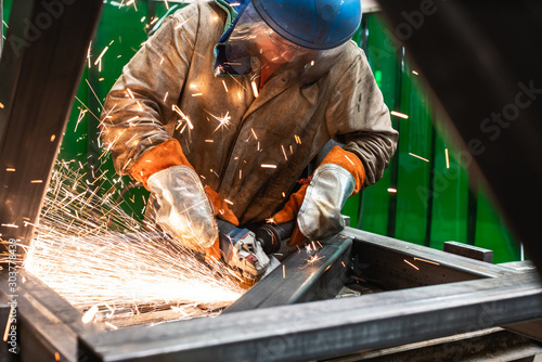 Metalworker working with angle grinder Canvas