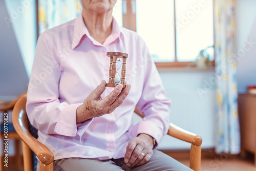 Cuadros en Lienzo Senior in nursing home holding a hourglass - time is running up