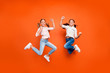 Leinwanddruck Bild - Full length photo of positive cute two children girls jump celebrate victory in school contest raise fists show strength wear white shirt denim jeans isolated orange color background
