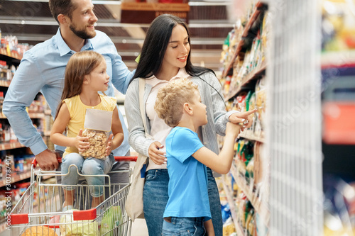 Daily Shopping. Family of four in the supermarket with cart choosing pasta smiling joyful
