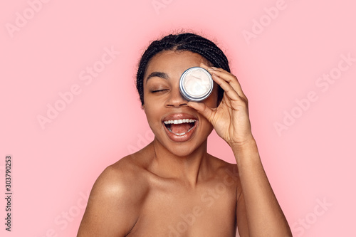 Fotobehang Spa Beauty Concept. Young african woman isolated on pink covering eye with cream jar laughing cheerful