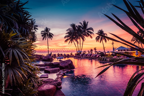 Fototapeta Stunning sunset view with palm trees reflecting in swimming pool in luxury island resort in Thailand obraz
