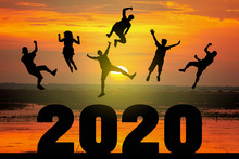 Silhouette Of Friends Jumping Celebrating New Year Over Number 2020 On Blurred Sunrise Background, Happy New Year Celebration Concept