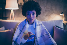 Portrait Of Astonished Crazy Afro American Girl Watch Horror Series Hold Remote Control Switch Channel Feel Voiceless Sit Divan Covered By Checkered Plaid Blanket In House Evening Indoors