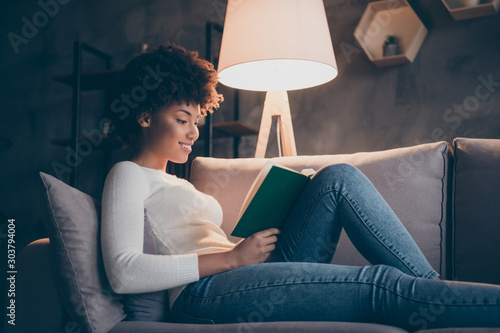 Fototapeta Photo of attractive dark skin curly lady holding favorite historic novel reading excited lying cozy couch wear casual sweater jeans outfit evening living room indoors obraz