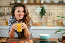 Young Woman In Kitchen. Beautiful Woman In Modern Kitchen Drinking Orange Juice.