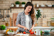Young woman in kitchen. Beautiful woman making salad.
