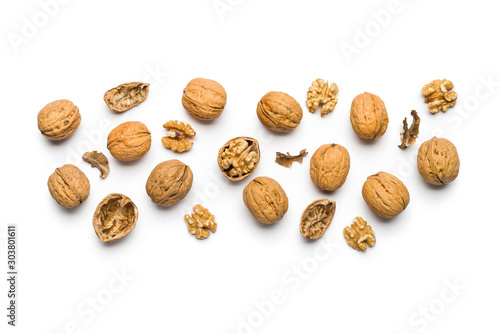 Fotografía top view of walnuts closed and broken scattered on a white background with copy