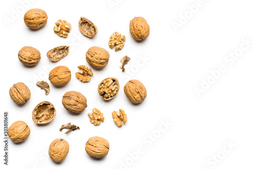 Obraz top view of walnuts closed and broken scattered on a white background with copy space - fototapety do salonu