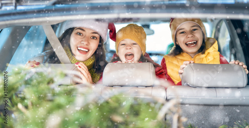 Mother, children and car on snowy winter nature - 303802876