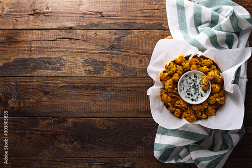Fotografía  cauliflower with breadcrumbs and spices with sour cream sauce and greens on wooden background with copy space