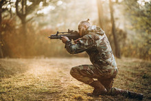 A Camouflage Soldier Playing Airsoft Outdoors In The Forest, Standing On One Knee, Aiming At The Rifle