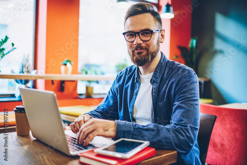 Valokuvatapetti Half length portrait of successful bearded designer smiling at camera while working on freelance at netbook