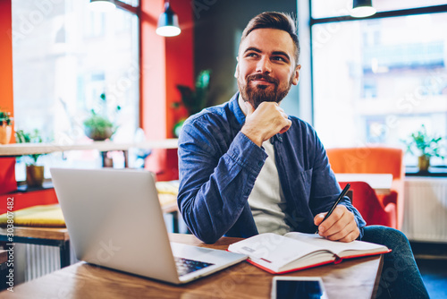 Smiling young bearded man writing plans in notebook and dreaming on business pro Wallpaper Mural