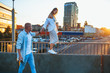 Tanned young caucasian couple, modern lovestory in film grain effect and vintage style. Sunset time. Walking on the city's street, summer evening and sunlight. Honeymoon concept. Toned in teal orange.