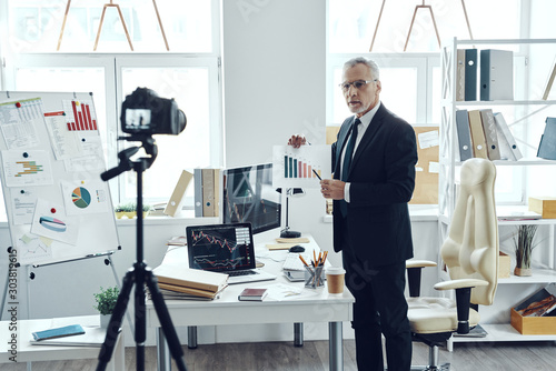 Fototapety, obrazy: Senior man in elegant business suit pointing at chart while making social media video