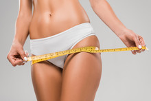 Cropped View Of Beautiful Slim Woman In Underwear Holding Measuring Tape On Hips Isolated On Grey