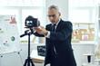 Senior man in elegant business suit adjusting video camera while making social media video