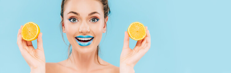 excited naked beautiful woman with blue lips holding orange halves isolated o...