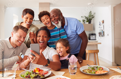 Fotografiet Multi-Generation Mixed Race Family Posing For Selfie As They Eat Meal Around Tab
