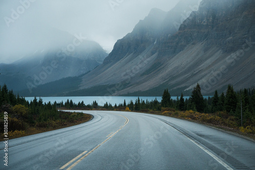 Scenic road trip with rocky mountain and lake in gloomy day Fototapete