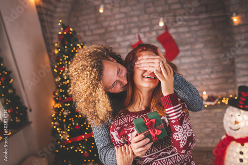 Pinturas sobre lienzo  Husband surprising wife with Christmas present