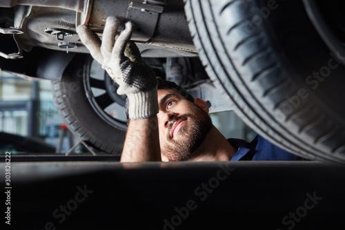 Fotografía  Mechatroniker bei der Reparatur von Auto Auspuff