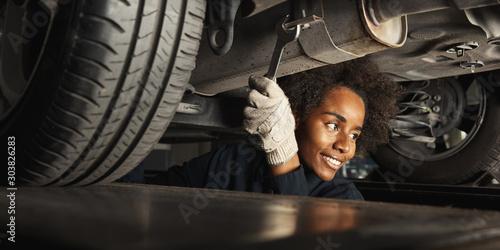 Fotomural  Afrikanische Frau als Mechatroniker unter Auto